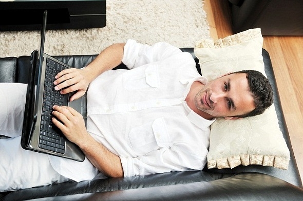 Portrait of a relaxed young guy using laptop at home indoor